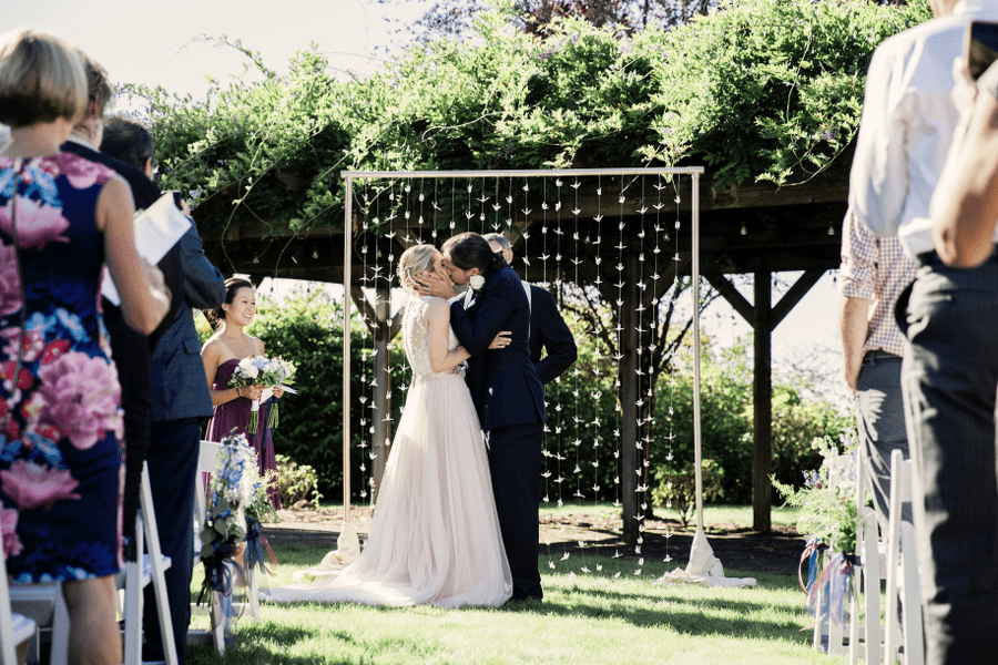 Outdoor Wedding Bride and Groom Kissing Under Wisteria