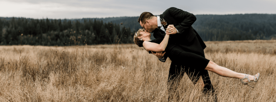 Couple Kissing in Grassy Meadow at Wonser Woods Wedding Venue